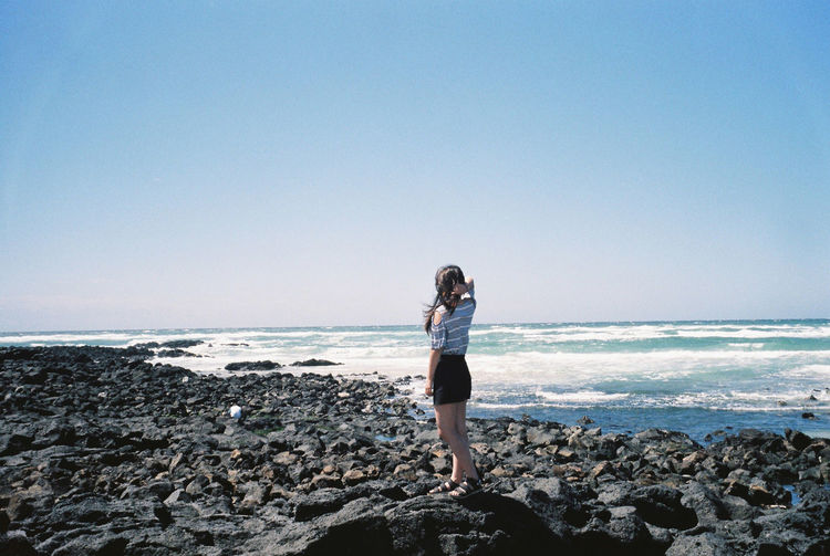 Rear view of young woman standing at seaside against clear sky