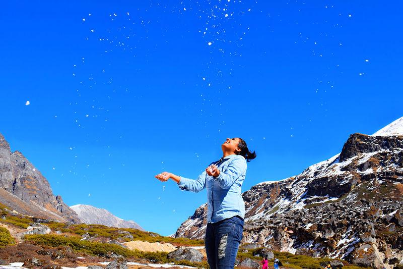Full length of man standing on rock against blue sky