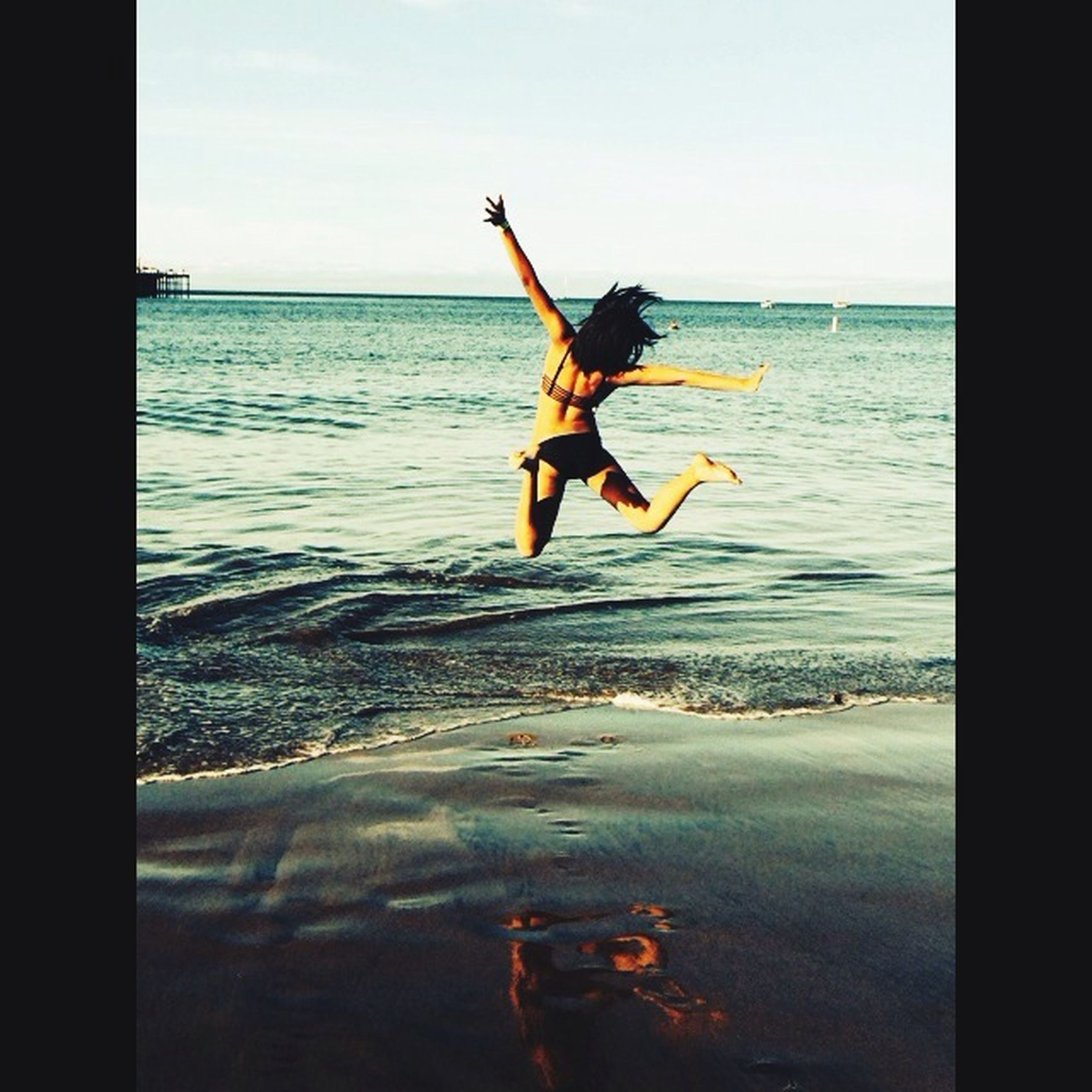 water, sea, full length, lifestyles, leisure activity, jumping, mid-air, enjoyment, horizon over water, fun, arms outstretched, vacations, vitality, motion, freedom, sky, carefree, skill
