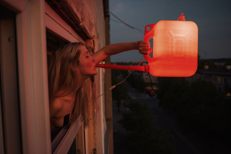 Young woman drinking from red illuminated container against sky