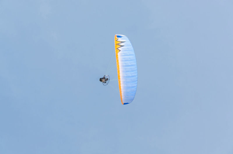 Low Angle View Of Parachute Flying Against Clear Blue Sky