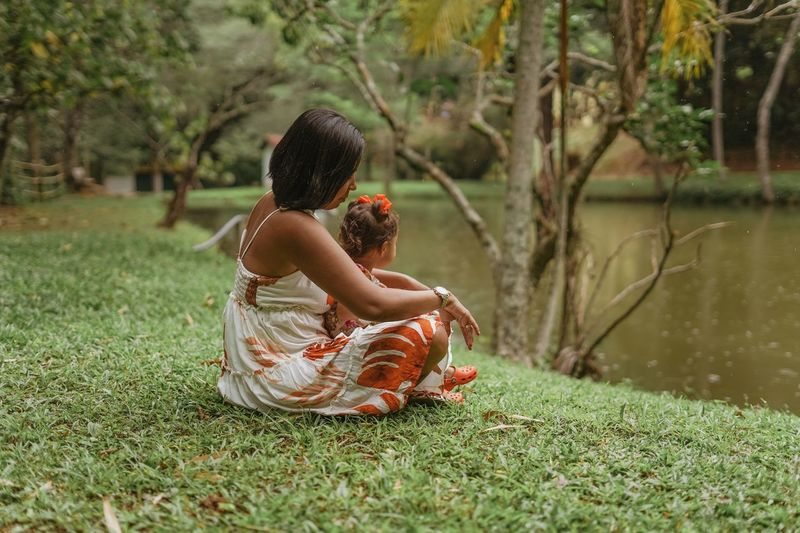 Full length of mother and daughter sitting on grass by pond at park