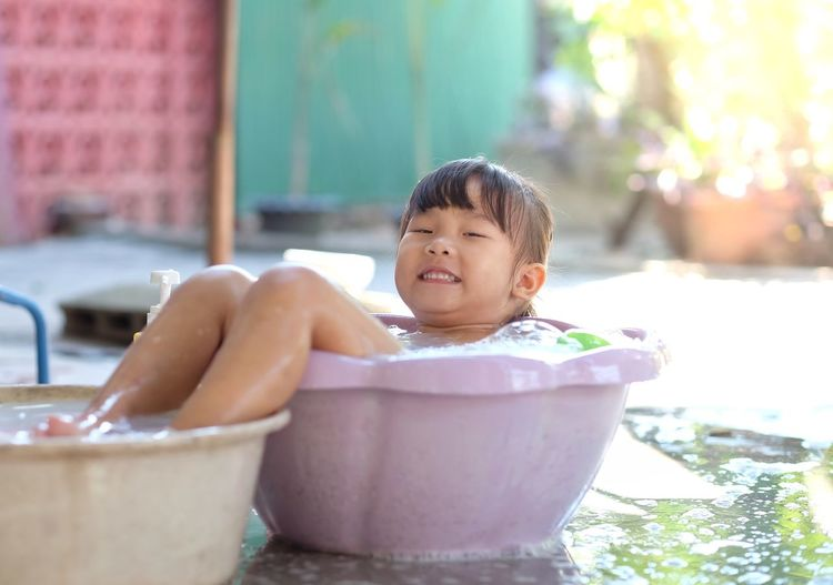 Little girl is smiling and playing water in the plastic basin happily in the garden. Basin Tub Bathtub Girl Child Kids Cute Childhood Child One Person Men Lifestyles Real People Leisure Activity Portrait Focus On Foreground Innocence Day Water Nature Front View Sitting Outdoors