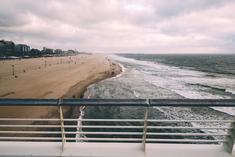 High angle view ofandy beach at sunset a cloudy day of summer from pier Architecture Beach Beauty In Nature Cloud - Sky Cloudy Day Handrail  High Angle View Horizon Over Water Nature No People Outdoors Pier Sand Scenic Scenics Sea Sky Storm Storm Cloud Sunset Tranquility Water Wave Waves