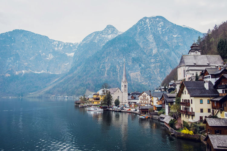 Town by lake and mountains against sky