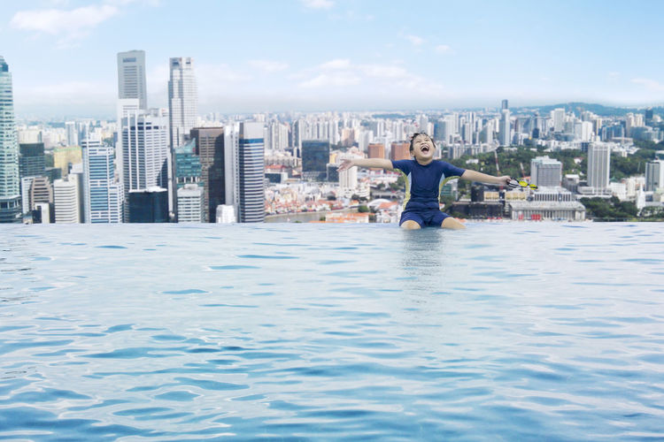 Happy boy with arms outstretched sitting on infinity pool against cityscape