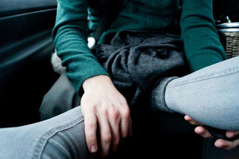 Low section of woman with man in car