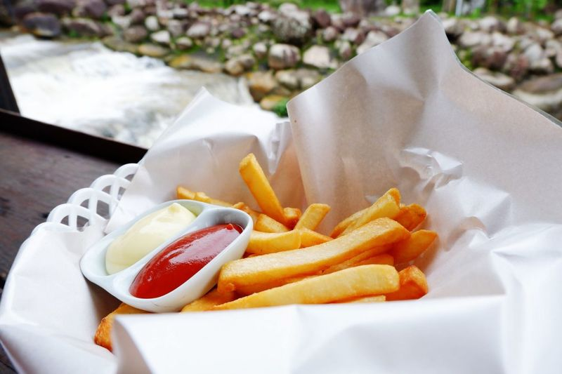 Close-up of french fries and sauce in paper