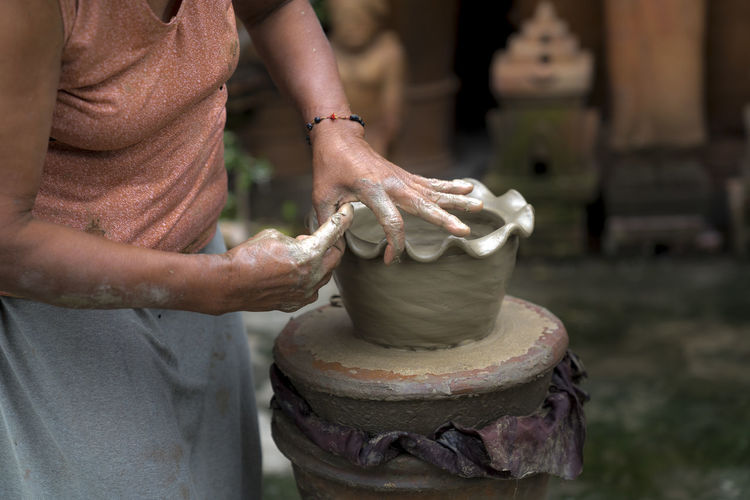 Midsection of woman working on pottery wheel