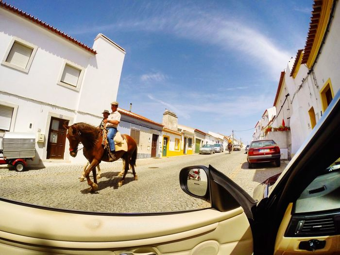Street in the city of Portel, central Alentejo, 39 km from Evora, Portugal. Portugal Alentejo Portel Transportation Horse Streetphotography Street Architecture Building Exterior Built Structure City Sky Full Length The Street Photographer - 2018 EyeEm Awards Nature People Women Men Lifestyles Transportation Leisure Activity Cloud - Sky Day Building Real People Sunlight Adult Mode Of Transportation