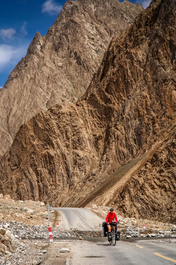 Woman riding bicycle on road against mountains