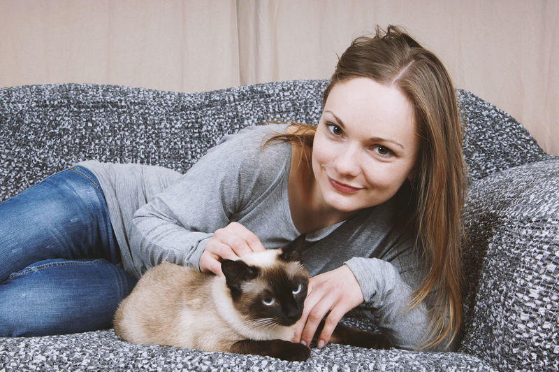 Portrait of woman with cat lying on sofa at home