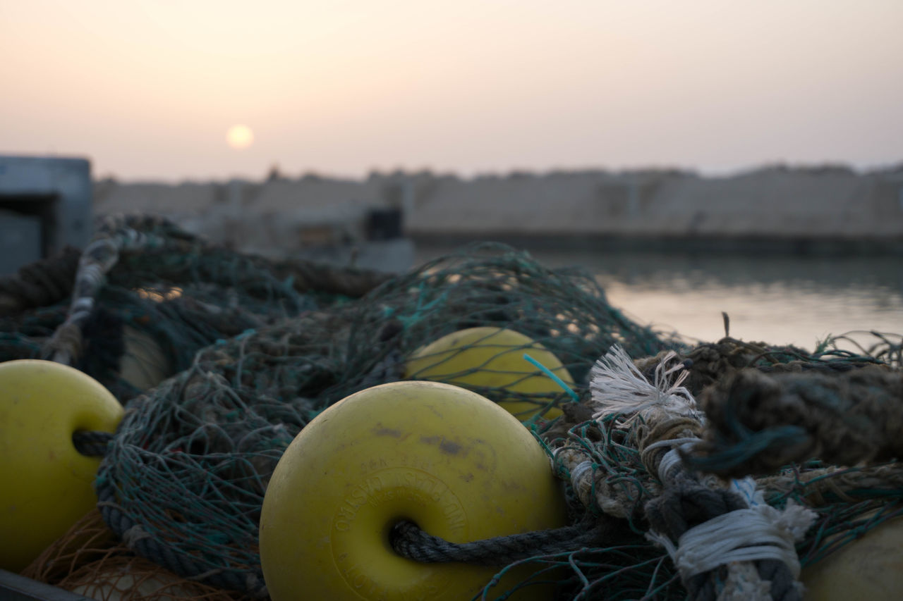 rope, fishing net, fishing industry, harbor, fishing equipment, no people, buoy, pier, sunset, nautical vessel, fishing tackle, outdoors, water, tied knot, moored, river, strength, tied up, nature, sky, beauty in nature, day, close-up