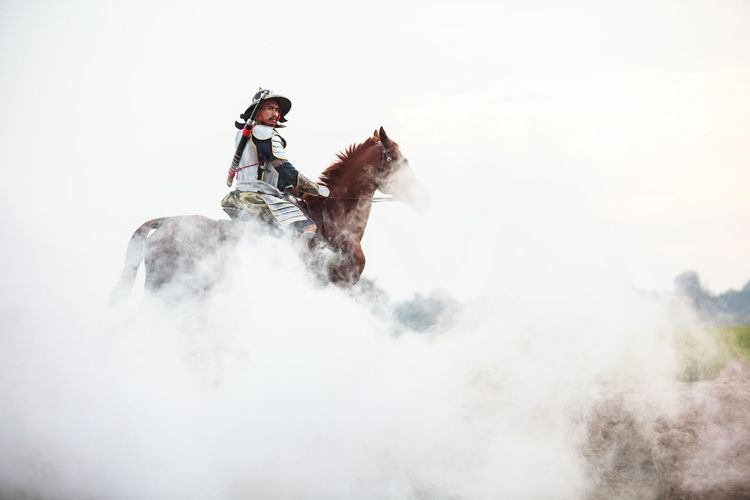 Low Angle View Of Warrior Riding Horse In Foggy Weather
