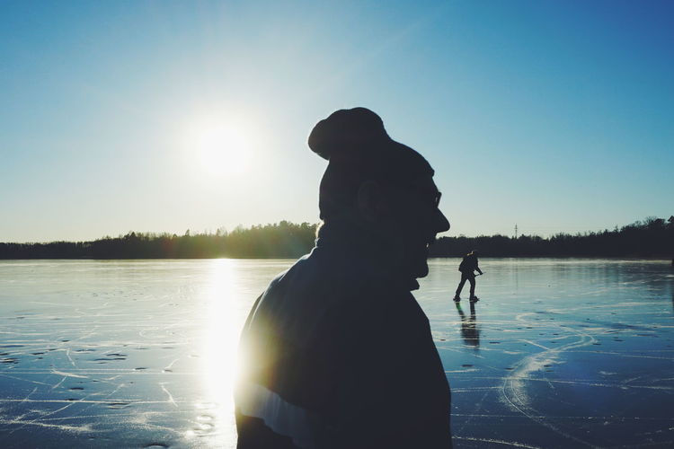 Silhouette senior man standing by lake against clear blue sky