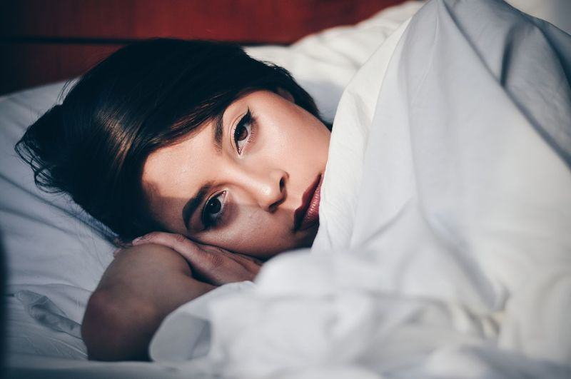 Close-up portrait of young woman lying on bed