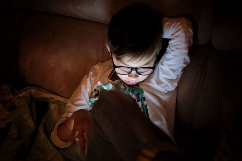 Boy using mobile phone on sofa at home