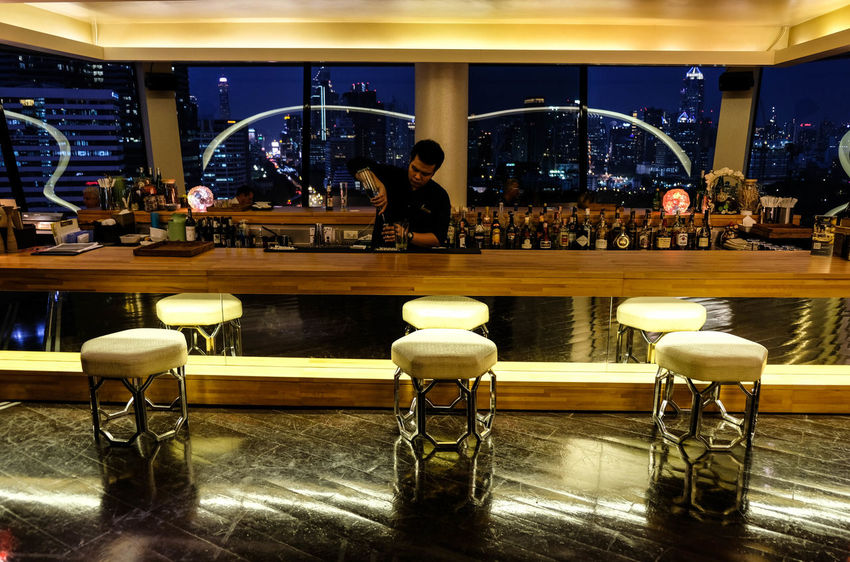 22nd floor Kitchen & Bar of Dusit Thani Bangkok Hotel Light Bar - Drink Establishment Bar Counter Cafe Chair Drink Hotel Indoors  Lifestyles Men Night People Real People Restaurant Shadow Table