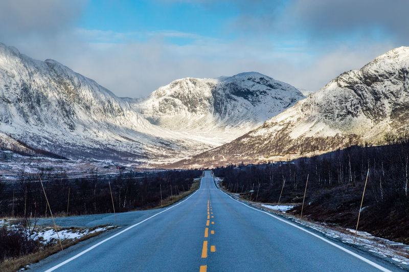 Road amidst snowcapped mountains of norway against sky