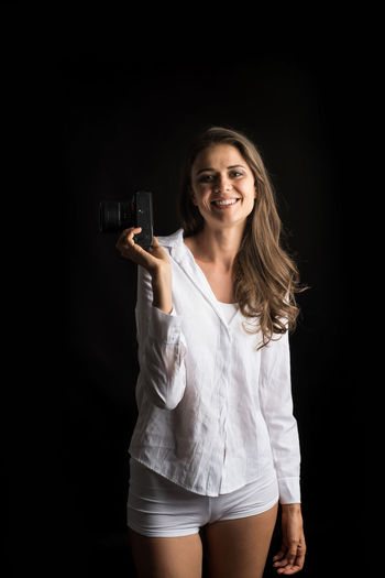 Smiling Holding Happiness Three Quarter Length Standing One Person Studio Shot Young Adult Portrait Indoors  Women Emotion Teeth Toothy Smile Hair Adult Black Background Looking At Camera Front View Cheerful Hairstyle Beautiful Woman