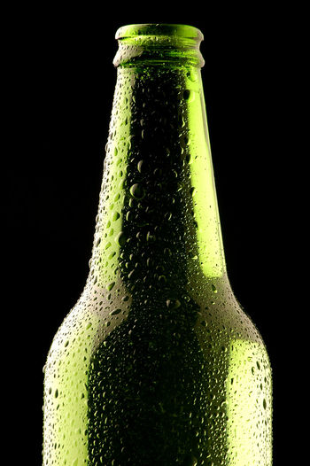 Close-up of green glass bottle against black background