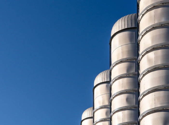 Low Angle View Sky Clear Sky Factory Industry Blue Copy Space No People Nature Built Structure Day Architecture Building Exterior Metal Silo Sunlight Outdoors Fuel And Power Generation Storage Tank Agriculture Silver Colored Chemical Plant Business
