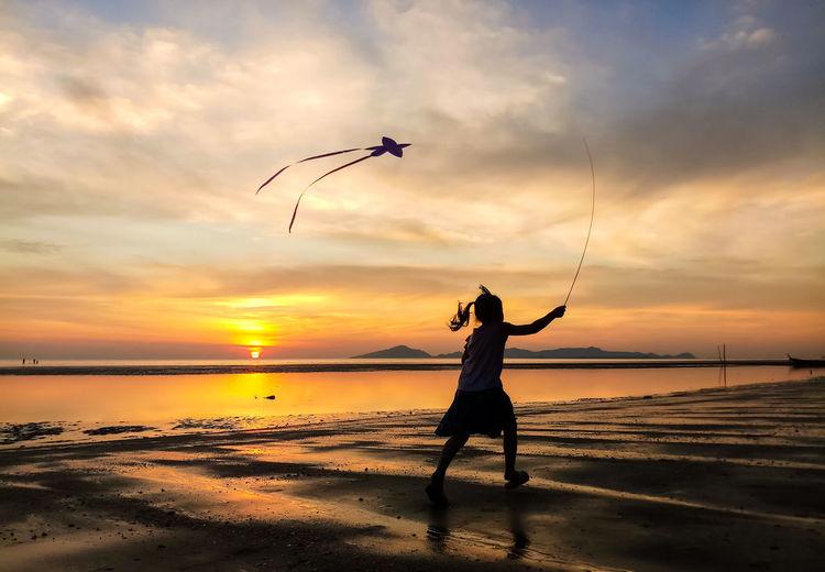 Silhouette girl flying kite at beach against sky during sunset