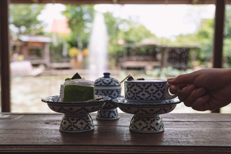 a hand holding a cup of hot milk with a piece of cake in an antique Thai traditional benjarong style containers Retro Restaurant Plate Pattern Old Mug Milk Luxury Kitchenware Hand Gift Food Eat Drink Dish Dessert Design Delicious Decoration Decorate Decor Cup Cuisine Coffee Closeup Close Clay Classic Ceramic Cake Cafe Blue Benjarong Beautiful Bakery Background Asian  Art Antique Ancient