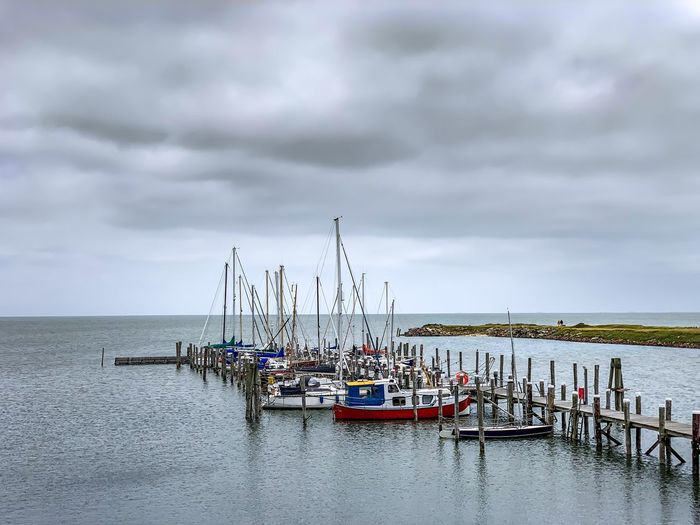 Fishing boats in sea against cloudy sky