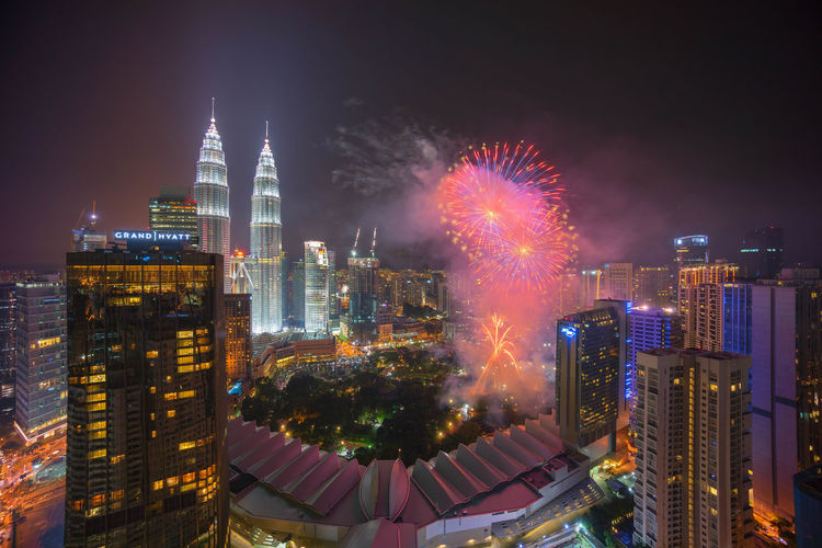 Scenic view of firework display over city at night