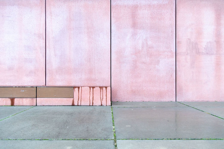 Empty footpath against building wall