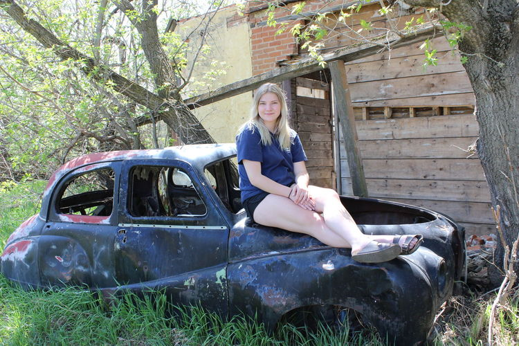 Portrait of smiling young woman sitting on wrecked vintage car