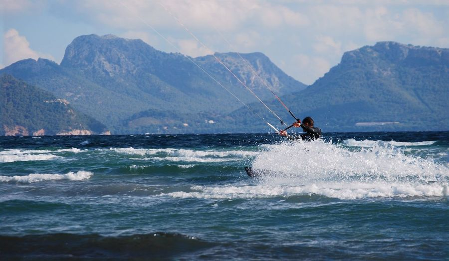 Man kiteboarding on sea by mountains against cloudy sky