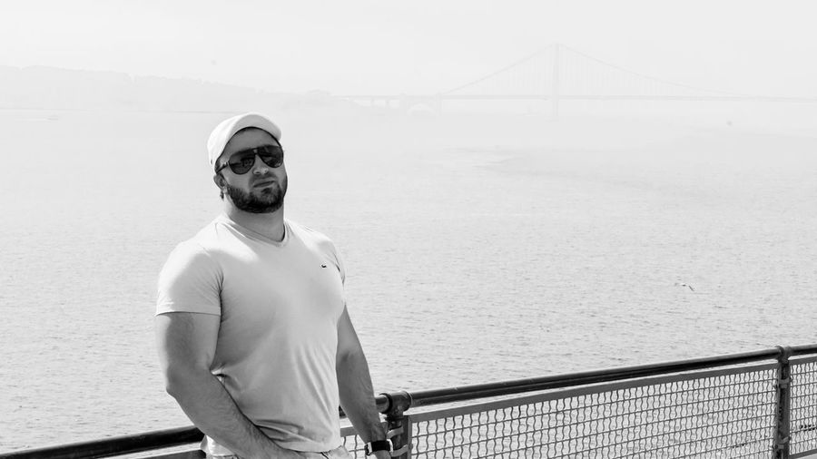 Portrait of man standing on bridge over sea against sky