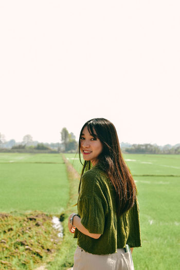 Side view of smiling young woman standing on field