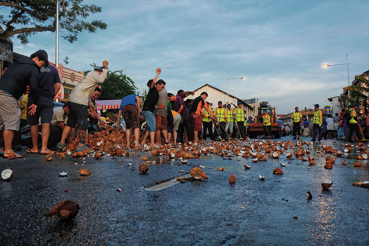 People breaking coconuts on road in city against sky