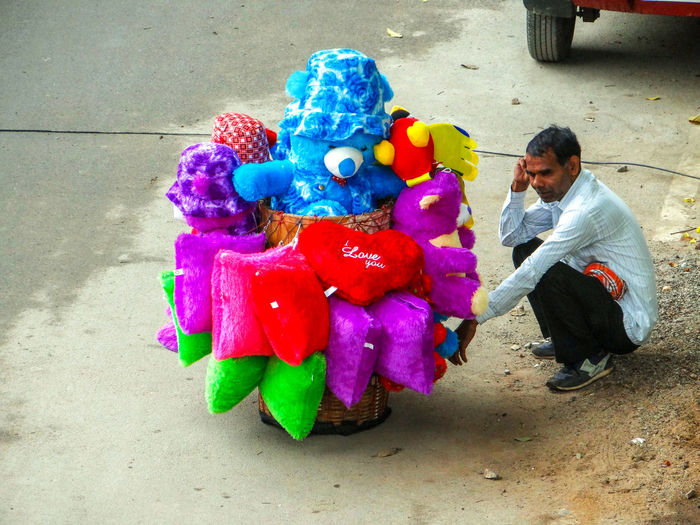 SELLER OF STUFFED TOYS IN THE STREET Roadside Street Basket Off Stuffed Toys Pensivemoments Resting Seller In The Streets For Sale In The Street Stuffed Toys Multi Colored Men Holi Working Street Art Colorful My Best Photo