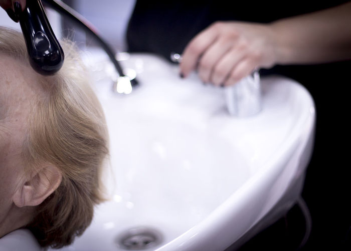 Cropped image of woman by sink at hair salon