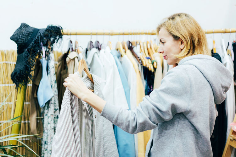 A woman is holding a shirt on a hanger in a clothing store and is about to try it on.
