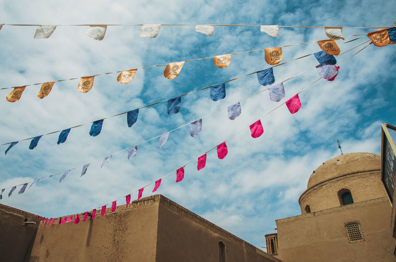 Low angle view of buntings hanging in city against sky