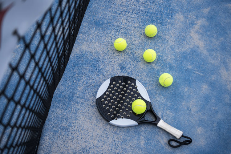 Paddle tennis racket and balls in court