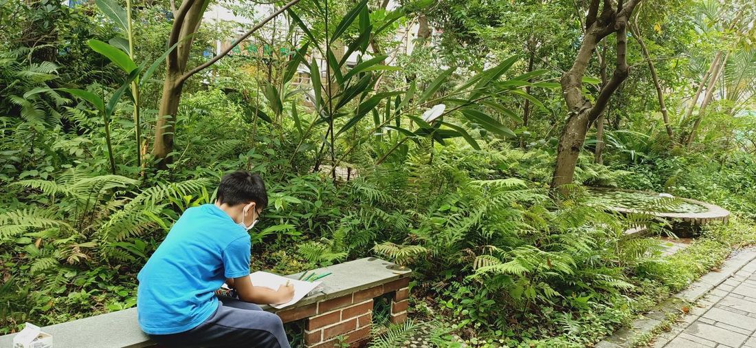 High angle view of boy drawing on book outdoors