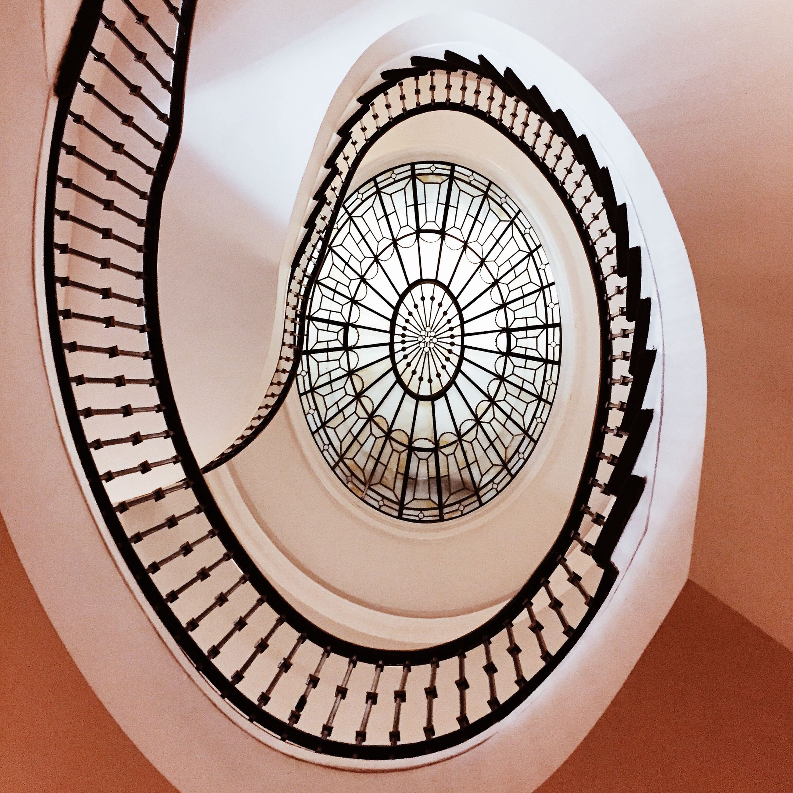 indoors, architecture, built structure, low angle view, directly below, staircase, spiral staircase, steps and staircases, spiral, railing, ceiling, steps, pattern, design, geometric shape, circle, skylight, architectural feature, building, modern