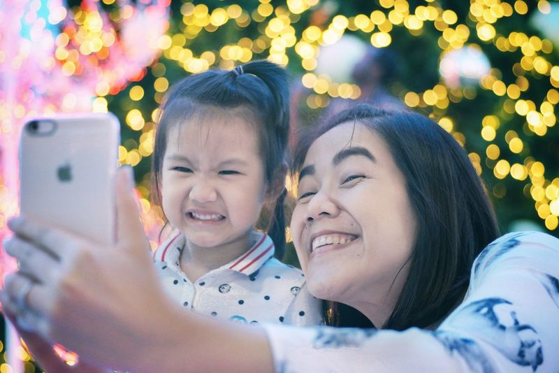 Smiling Mother And Daughter Taking Selfie With Smart Phone Against Illuminated Christmas Tree
