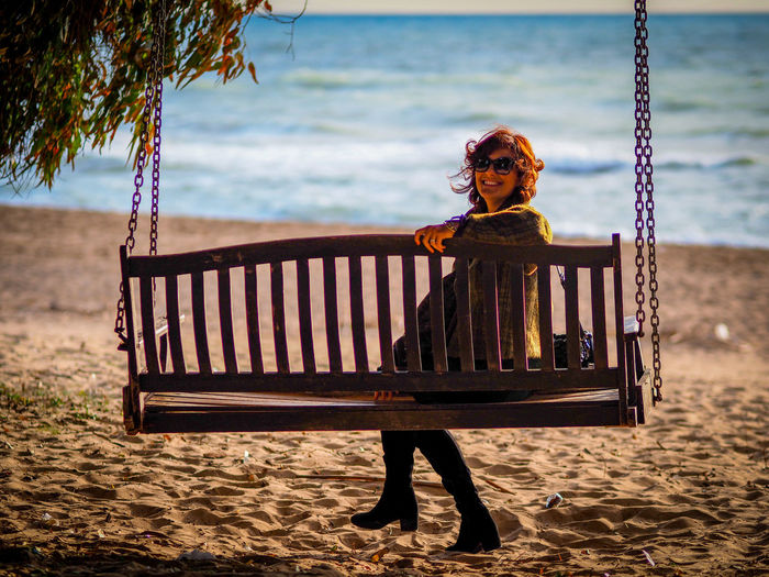 Smiling woman sitting on swing at beach