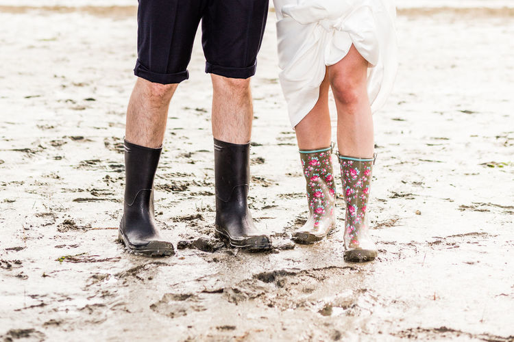 Low section of man and woman wearing rubber boots while standing mud