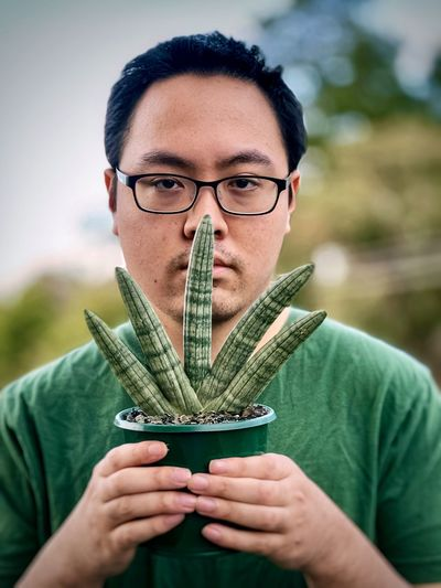 Portrait of young man holding fan shaped succulent plant in a pot against trees and cloudy sky.