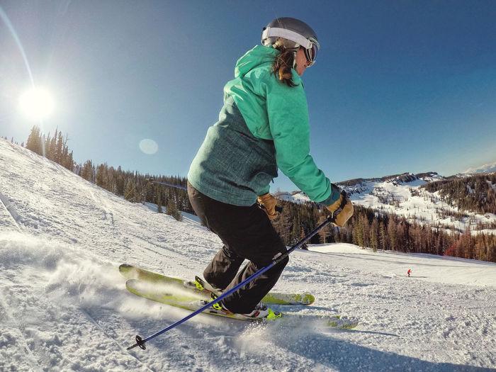 Full length of man skiing on mountain against sky