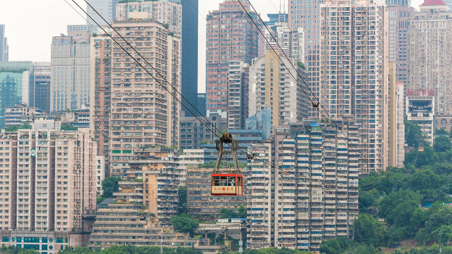 Low angle view of overhead cable car against buildings in city