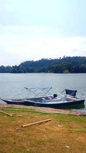 Lake of Banding in Malaysia Water Lake Tranquility Beach Nature Outdoors No People Day Scenics Floating On Water Landscape Beauty In Nature Nautical Vessel Bird Sky Low Tide Tree Animal Themes boat jungle